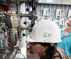 Senior Technician Bill Bray (front) and Master Technician Bob Lyons (back) inspect and service the biomass pretreatment reactor in NREL's Integrated Biorefinery Research Facility. Credit: Dennis Schroeder